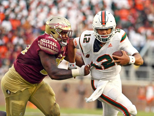 Miami quarterback Malik Rosier (12) runs the ball past Florida State defensive tackle Demarcus Christmas (90) during the second half at Doak Campbell Stadium.