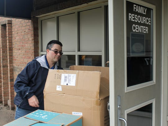 Andrew Sigler brings boxes of donated items into the Wayne-Westland Community Schools Family Resource Center. He's from Livonia.