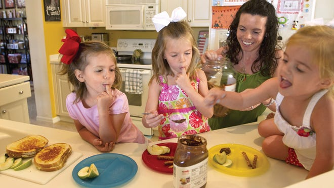 Parker, 4, left, Peyton, 6, center, and Emerson, 2, sample some Nutella while making lunches with their mom, Melissa Hemmer.