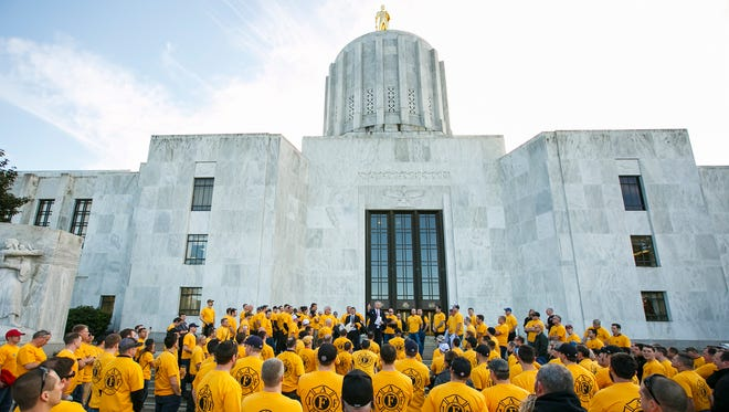 About 300 firefighters from across the state listen as Karl Koenig, legislative director for the Oregon State Fire Fighters Council, addresses them from the steps of the Capitol on Monday, Feb. 13, 2017. Several hundred PERS members, which include teachers, state workers, firefighters, nurses and public safety employees, turned out to oppose two bills that would affect their retirement system.
