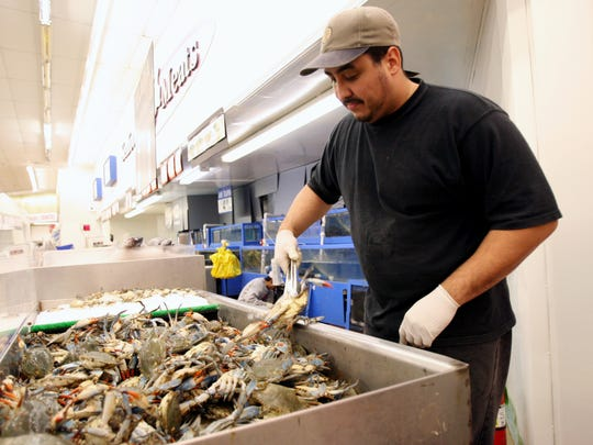Tommy Rivera wrangles live crab at Saraga International