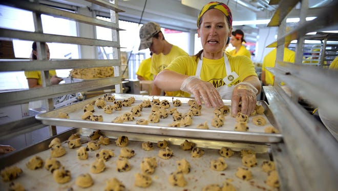 Jean Olson, sister-in-law to Martha Rossini Olson, arranges cookie dough on sheets before they go to the oven. Jean Olson has worked at Sweet Martha's Cookie Jar for approximately 20 years.
