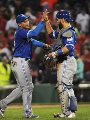 Blue Jays' Ezequiel Carrera high fives Russell Martin after defeating the Red Sox.