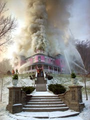 In this Dec. 24, 1996 photo, firefighters from several Jackson County communities fight the flames at the Mont Rest Bed and Breakfast in Bellevue.