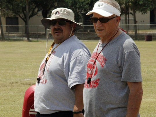 Indians coaches John Weber, right, and Israel Gallegos, look on during the first day of spring football practice at Immokalee High on Monday, April 25, 2016. (J. Scott Butherus)