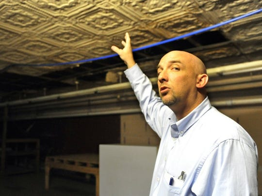 In this file photograph, Beau Dameron points out antique ceiling tiles that he and his partners will restore at their downtown retail store, 922 Indiana Ave. The partners said putting in the grocery store is their top priority to serve residents and downtown business employees alike.