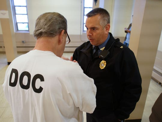 Warden Dana Metzger at James T. Vaughn Correctional Center speaks with an inmate before an Inmate Advisory Committee meeting.