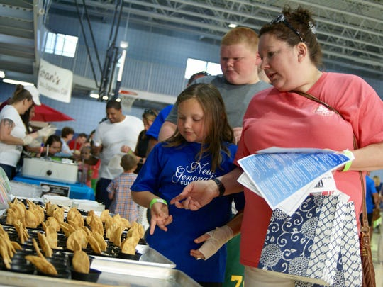 Heather Lilley and daughter, Jordyn, look at a selection of caramel apple walnut cream cheese at the Starr Ranch booth during the ninth annual Taste of Gallatin held at the Gallatin Civic Center on Thursday, June 2.