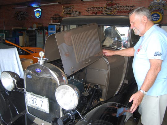Al Duebber, founder and co-chairman of Rollin' on the River charity car show, polishes a 1929 Ford Model A which will be featured at the event, which will be July 23.