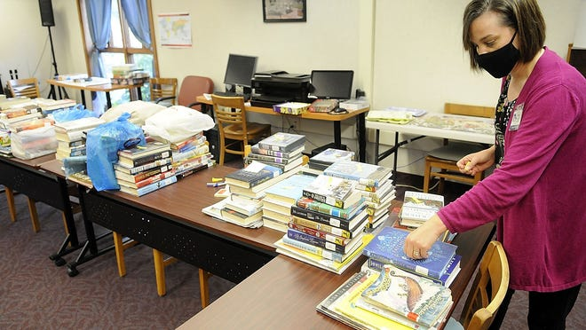 Loudonville Public Library employee Caitlyn Petrie places a note on a stack of returned books in the Golden Center with the date of their return. After 72 hours, the items can be safely put back in circulation.