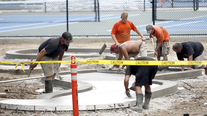 Workers from Lee Construction smooth out the concrete on one of the Brookside Park Miniature golf course's holes on Thursday as the renovation work continues.