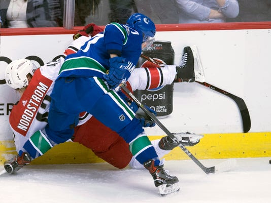 Vancouver Canucks right wing Nikolay Goldobin (77) puts Carolina Hurricanes left wing Joakim Nordstrom (42) against the boards during the first period of an NHL hockey game Tuesday, Dec. 5, 2017, in Vancouver, British Columbia. (Jonathan Hayward/The Canadian Press via AP)
