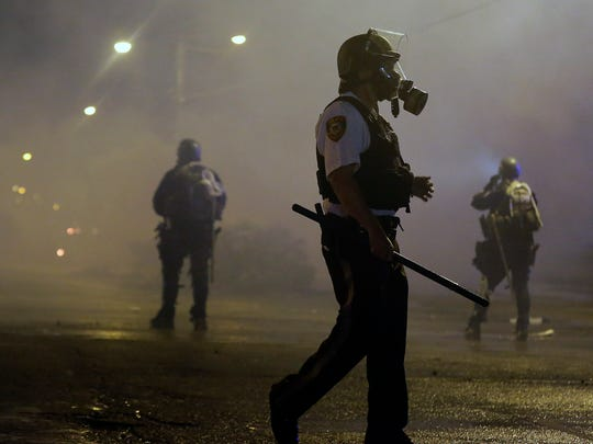 Law enforcement officers wait to advance Sunday, Aug. 17, 2014, after firing tear gas to disperse a crowd protesting the shooting of teenager Michael Brown last Saturday in Ferguson, Mo.