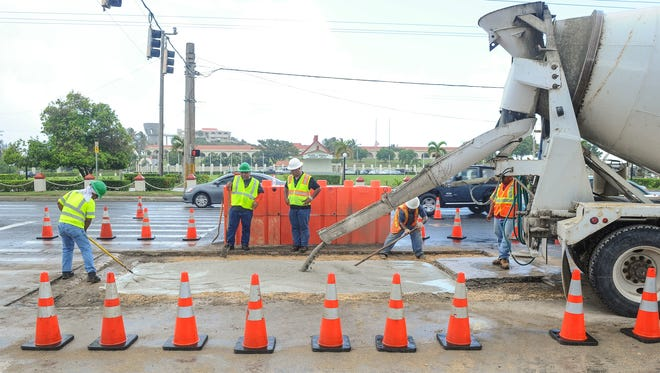 Workers level out a concrete slurry mix to cover an underground wastewater pipe repair at the Adelup intersection on Marine Corps Drive on Tuesday, July 12. The water flowing from the broken 18-inch pipe, created a sinkhole on Monday, that forced northbound motorists to a reduced number of lanes, as Guam Waterworks Authority employees made the repairs.