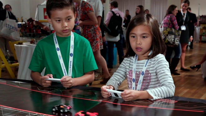 Evan and Jillian, of EvanTubeHD, test the Anki Drive battle-racing game at the TTPM Holiday Showcase in New York on Oct. 1.