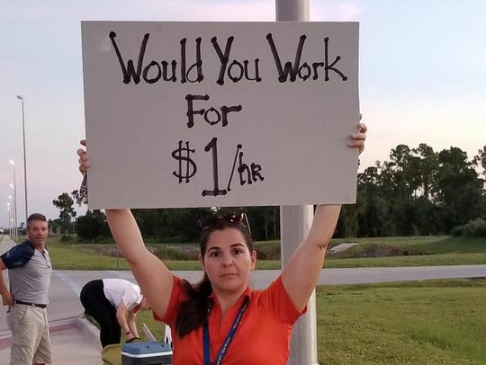 A picketer Wednesday outside Punta Gorda Airport.