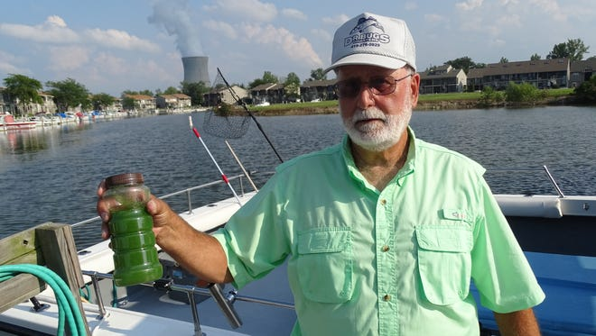 Oak Harbor charter boat captain Dave Spangler holds up a bottle of green, algae-filled water taken from Lake Erie in 2015. Spangler is among those opposing cuts in the Great Lakes Restoration Initiative.