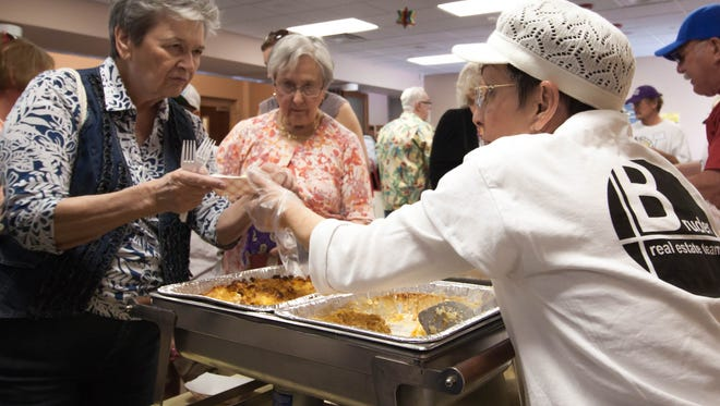 Volunteer Marianne Rosenthan, right, serves kugel to Marleme Lavetts, left, and Nancy Jenkins during the Jewish Food and Folk Festival on Sunday at Temple Beth-El.