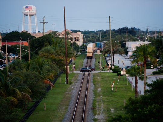 A freight train rolls southbound on the Florida East Coast railroad tracks, as seen from the Roosevelt Bridge, in downtown Stuart on Aug. 5, 2014. Under House Bill 525, costs associated with the construction and maintenance of at-grade rail crossings — as well as expenditures for improvements and upgrades of at-grade rail crossings — would be shifted from local governments to passenger rail companies.
