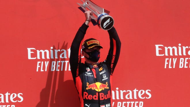 Red Bull driver Max Verstappen of the Netherlands holds up the trophy on the podium after taking first place in the 70th Anniversary Formula One Grand Prix at the Silverstone circuit, Silverstone, England, Sunday, Aug. 9, 2020.