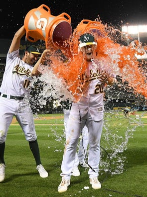 MAY 19:  Mark Canha is soaked with Gatorade by Adam