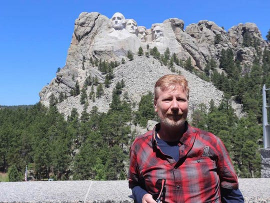 Ronald Wilmoth poses in front of Mt. Rushmore while
