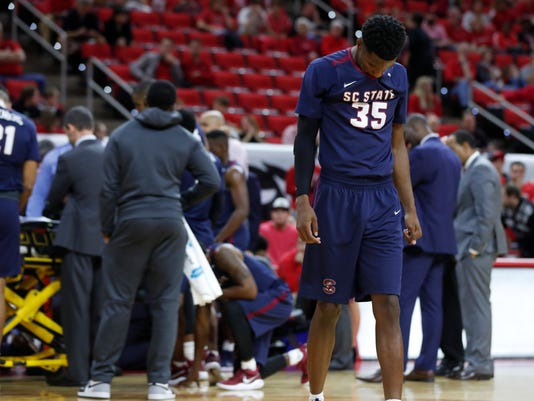 FILE - In this Dec. 2, 2017, file photo, South Carolina State players, including Damani Applewhite (35), react as Tyvoris Solomon is attended to after he was injured during the first half of an NCAA college basketball game against North Carolina State in Raleigh, N.C. Solomon, who collapsed on the court during the game last week, has been released from the hospital. (Ethan Hyman/The News & Observer via AP, File)
