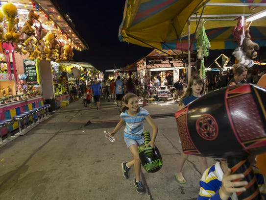 Kids play the carnival game to win prizes during Sawdust