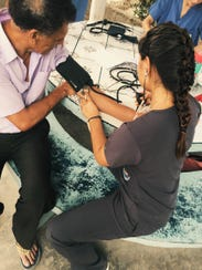 Tessa Arendt checks the blood pressure of a patient