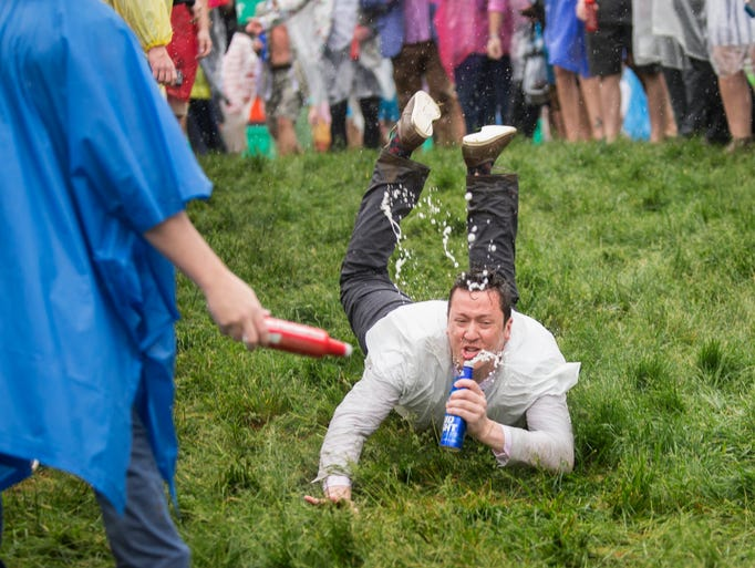 A man dove onto the wet ground with a beer in his hand,