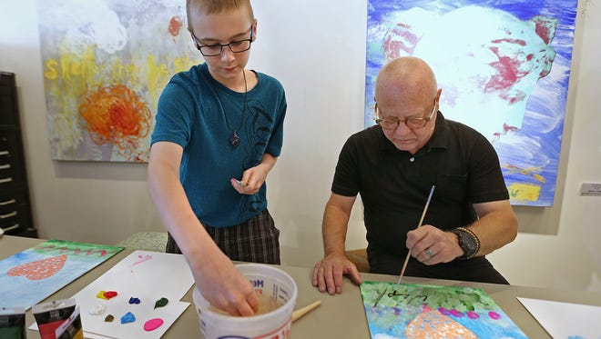 Cooper Davis, 12, and Walter Knabe paint side by side at Knabe's studio in south Broad Ripple. Knabe partnered with the Indiana Children's Wish Fund to paint with children who created and took home their own piece of art, and contributed to pieces to be auctioned off later.