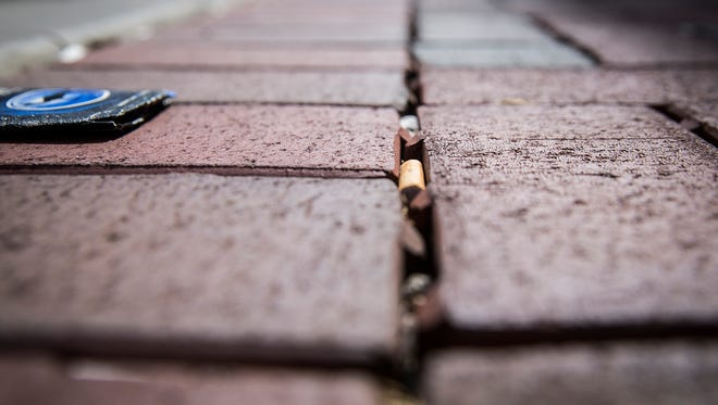 Gaps between brick pavement on Walnut Street collect cigarette butts and other trash Thursday.