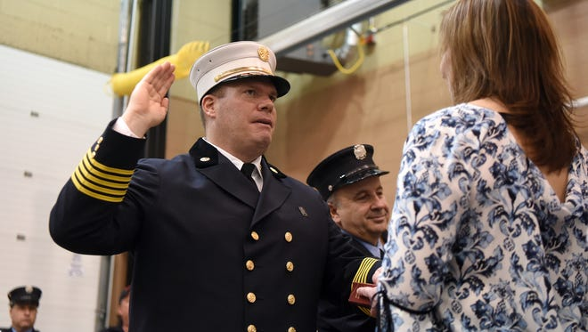 Paterson's new fire chief Brian McDermott takes the oath of office while his wife, Shannon McDermott holds the Bible, on Monday, January 29, 2018 at Paterson's fire headquarters on McBride Ave.