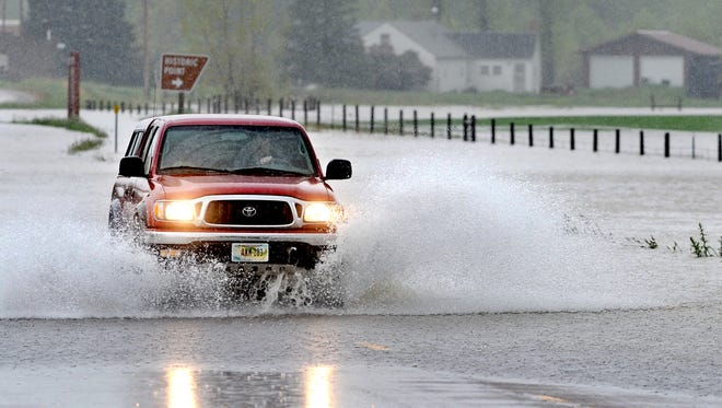 A motorist drives through flood water near the town of Sun River during the 2011 floods. TRIBUNE PHOTO/RION SANDERS