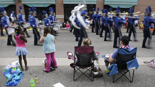 Spectators watch as marching band members file down St. Germain Street during Saturday's Granite City Days parade in St. Cloud.