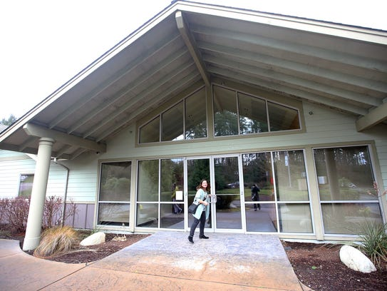 Erica Delma, development director at Holly Ridge Center, exits the Windsor Building on Kitsap Way on Friday. The center is purchasing the building.