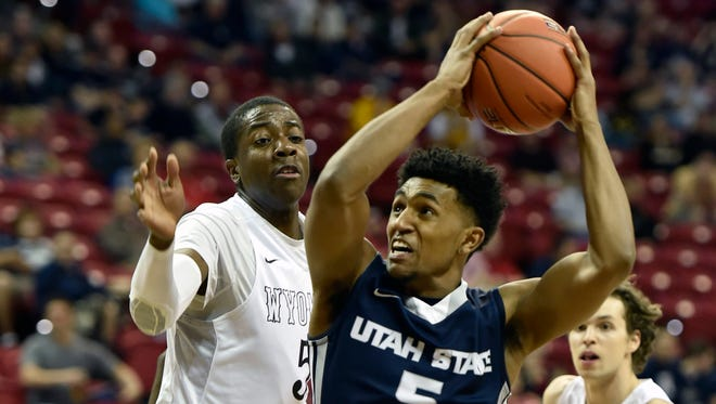 Utah State's Julion Pearre (5) drives to the basket against Wyoming's Alan Herndon during the first half of an NCAA college basketball game at the Mountain West Conference men's tournament Wednesday in Las Vegas.