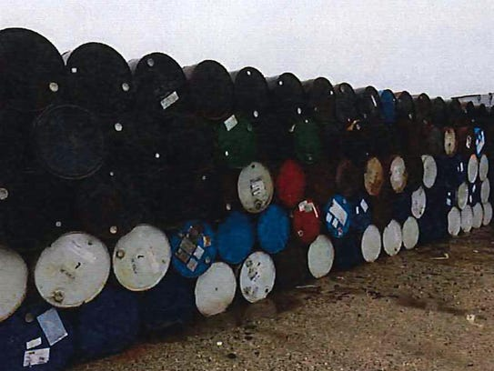 Fifty-five gallon drums are seen stored in a parking