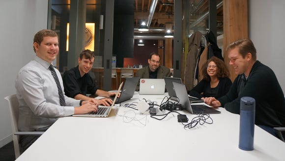Scott Bolte (middle) is flanked by DevCodeCamp graduates