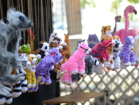 A row of marionettes hang from the top of Charles Zhang's vendor booth during a past Y Bridge Arts Festival at Zane's Landing in this file photo.