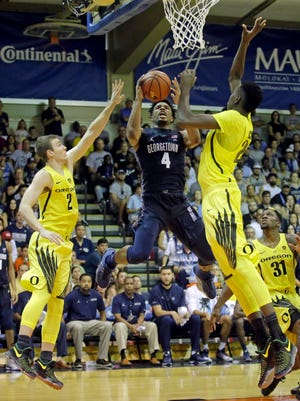 Georgetown guard Jagan Mosely (4) shoots as Oregon's Casey Benson (2) and Chris Boucher, right, defend in the second half in the Maui Invitational on Monday.