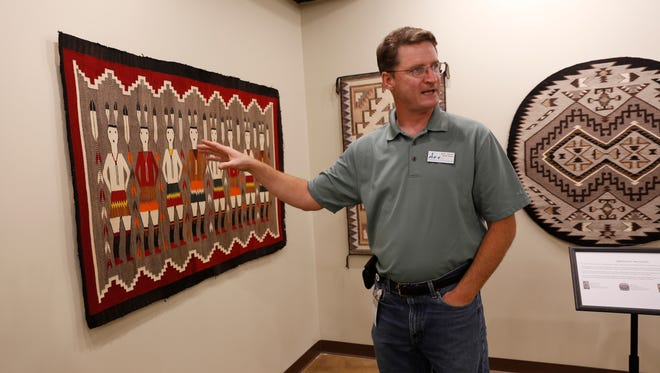"""Farmington Museum director Bart Wilsey points out some of the features of a weaving included in the exhibition """"Patterns from Places"""" on Thursday at the soon-to-open Museum of Navajo Art and Culture in Farmington."""