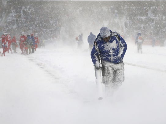 The New Era Stadium crew kept busy clearing snow during timeouts during the Buffalo Bills' 13-7 overtime win against the Indianapolis Colts.