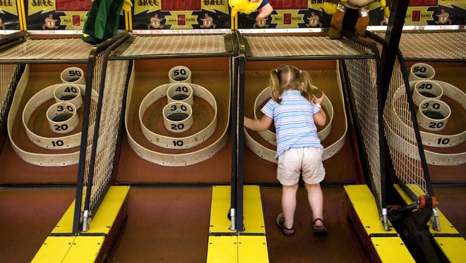 In this June 5, 2009, file photo, Ruby Self, of Grand Blanc, Mich., makes her way up the lane of a Skee Ball Inc. game machine to aim for a higher score in Burton, Mich.