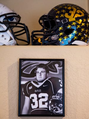 Marc Newberry's Naples High School helmet sits above his football photo at his home in Naples on Wednesday, May 3, 2017. Newberry, 20, was killed in a canal boat crash on April 28.