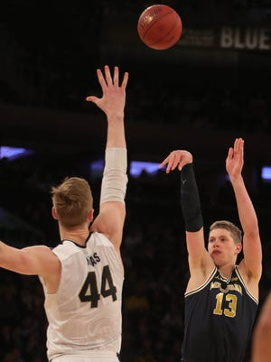 Michigan's Moritz Wagner scores against Purdue's Isaac Haas during the first half of the Big Ten tournament championship game Sunday, March 4, 2018 at Madison Square Garden in New York.