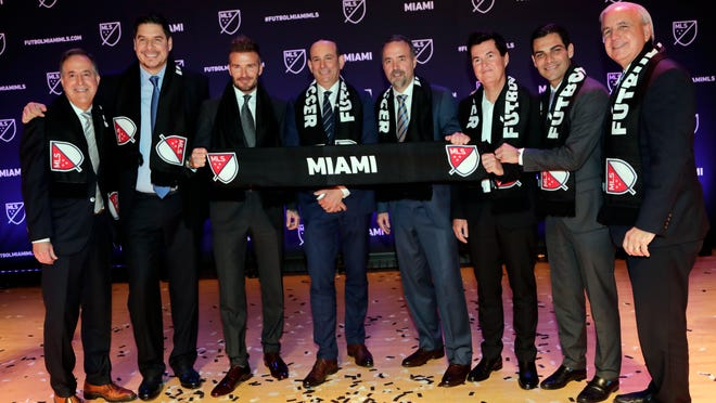David Beckham, third from left, poses for a group photo at an event where it was announced that Major League Soccer is bringing an expansion team to Miami, Monday, Jan. 29, 2018, in Miami. From left to right are Jorge Mas, Marcelo Claure, Beckham, MLS Commissioner Don Garber, Jose Mas, Simon Fuller, Miami Mayor Francis Suarez and Miami-Dade County Mayor Carlos Gimenez. (AP Photo/Lynne Sladky)