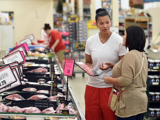 """Nikki Mitchell, left, and Sarah Reynolds discuss a grocery purchase during a recent shopping trip. The two say they sometimes get """"weird"""" looks, but most often it's not a big deal."""