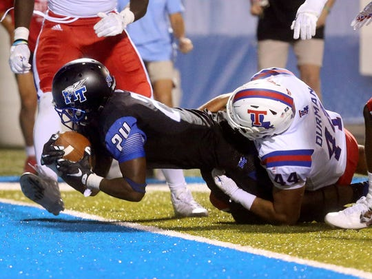 MTSU's Ty Lee (24) scores the game-winning touchdown as Louisiana Tech's Brandon Dunn (44) tries to hold him back.