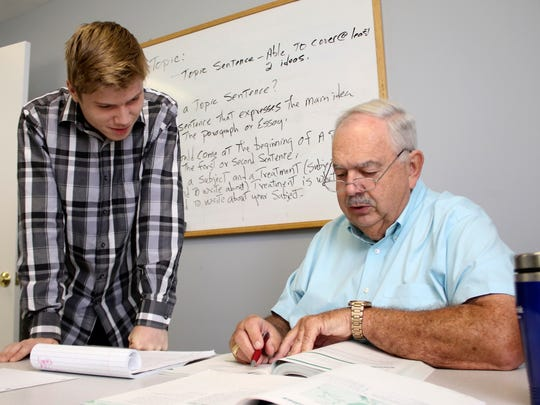 Xavier Arrant, a student enrolled in Workforce Essential's adult education program, gets assistance with an assignment from his teacher Howard Spurgeon. Spurgeon's students cannot efficiently access all the resources available to them due to slow internet connections in Houston County.
